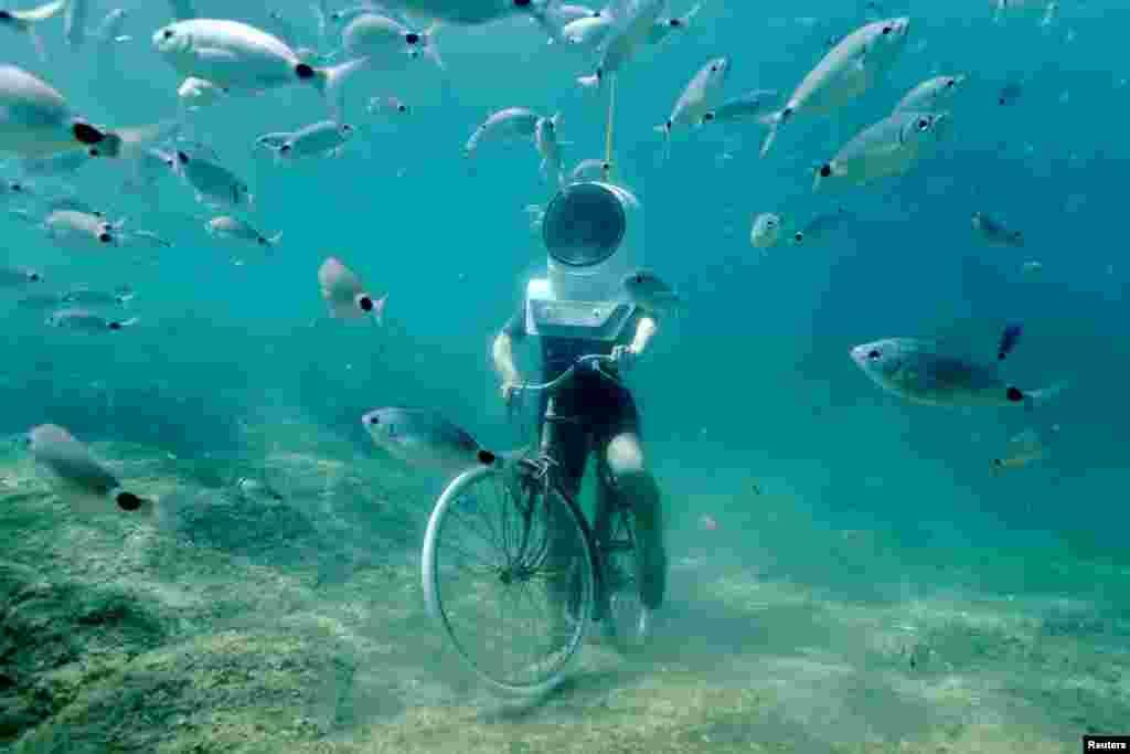 Seorang pengunjung berpose seperti sedang mengendarai sepeda dalam air di sebuah taman bawah air di kota Pula, Kroasia.
