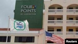 """Un drapeau américain et un drapeau de la compagnie militaire cubaine flottent près du logo d'un hôtel"""" Four Points by Sheraton """" à La Havane , Cuba , le 27 Juin , ici 2016."""