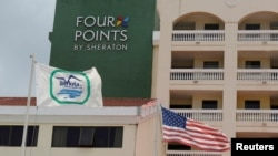 "A U.S. flag and a flag of the Cuban military-run hospitality company Gaviota flutter near the logo of a ""Four Points by Sheraton"" hotel in Havana, Cuba, June 27, 2016."