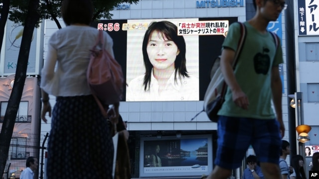 A portrait of Japanese journalist Mika Yamamoto is shown on a large monitor screen in Tokyo Tuesday, Aug. 21, 2012 during a TV news broadcast reporting her death in Syria.