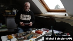 Guy Warein, a 70-year-old retiree, works on model trains in his home in Richebourg, northern France, Wednesday, Jan. 27, 2021. (AP Photo/Michel Spingler)