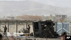 US soldiers, left, stand at the site of a suicide car bomber in Kabul, Afghanistan, October 29, 2011.
