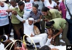 Polisi menyeret aktivis HAM Kuba dari kelompok Ladies in White yang berdemonstrasi menuntut pembebasan tahanan politik, di Havana, Kuba (20/3).