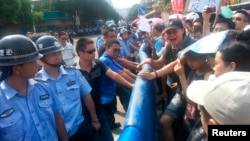 Police face off with demonstrators protesting plans for a nuclear facility in Jiangmen, Guangdong province, July 12, 2013.