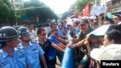 Polisi China berhadapan dengan demonstran yang memprotes rencana pembangunan fasilitas nuklir di Jiangmen, Provinsi Guangdong (12/7).