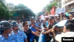 ຕຳຫຼວດປະເຊີນໜ້າກັບພວກເດີນຂະບວນ ປະທ້ວງແຜນການກໍສ້າງໂຮງງານ ຜະລິດເຊື້ອໄຟນິວເຄລຍ ທີ່ເມືອງ Jiangmen ໃນແຂວງ Guangdong (12 ກໍລະກົດ 2013)