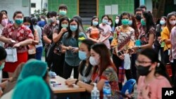 People line up as they wait for their turn to get a shot of the Sinovac COVID-19 vaccine during a mass vaccination at Putri Hijau Military Hospital in Medan, North Sumatra, Indonesia.