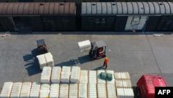 中國江西省九江火車站的一名工人正在裝卸從新疆運來的棉花。(2021年3月26日)