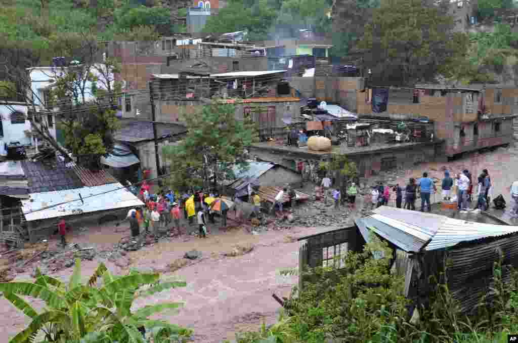 People look for bodies and salvage belongings after heavy rains triggered a landslide in a low income neighborhood in the city of Chilpancingo, Guerrero state, Mexico, Sept. 16, 2013.