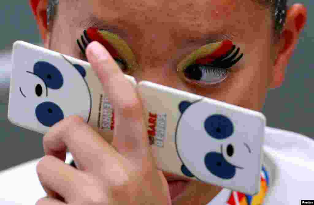 A Thai swimmer checks her makeup before the women's synchronized swimming duet free routine final of the Southeast Asian (SEA) Games at the National Aquatic Center, Kuala Lumpur, Malaysia.