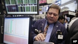 In this Sept. 9, 2011 photo, trader John Santiago works on the floor of the New York Stock Exchange.