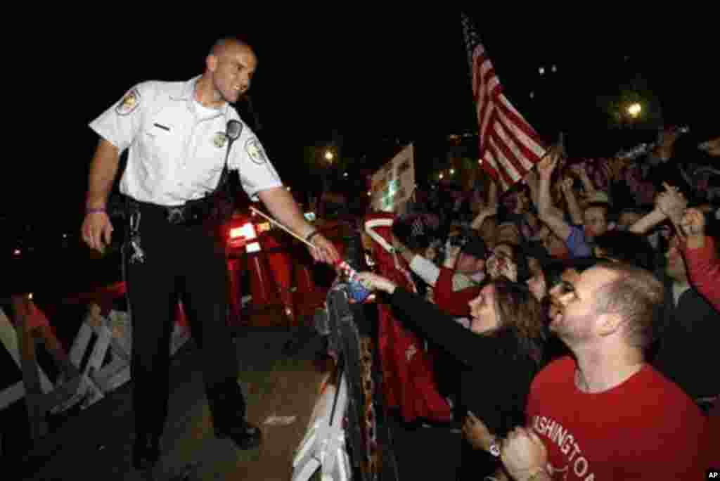 A U.S. Park Police officer is handed a flag as crowds celebrate on Pennsylvania Avenue in front of the White House in Washington, early Monday, May 2, 2011, after President Barack Obama announced that Osama bin Laden had been killed (AP Photo/Charles Dhar