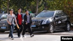 People walk past Cadillac cars outside a dealership in Beijing.