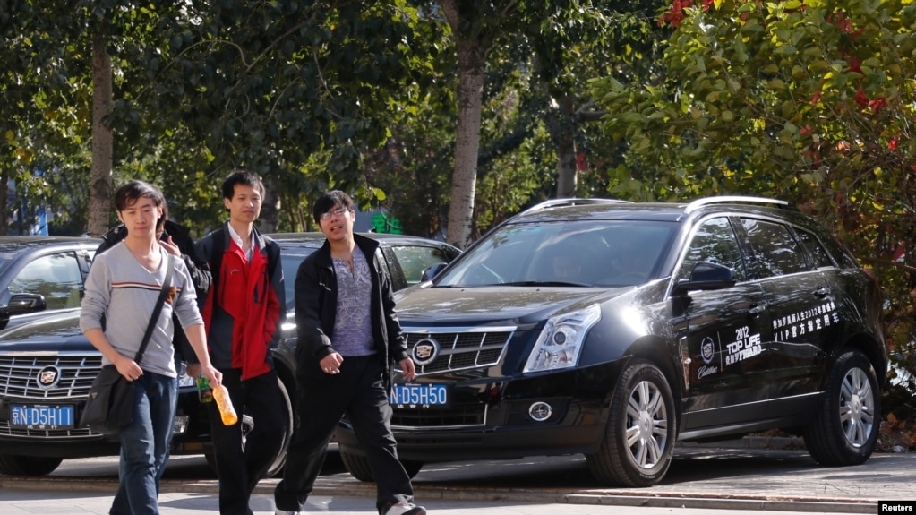 People walk past Cadillac cars outside a dealership in Beijing, October 31, 2012.