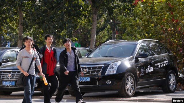 People walk past Cadillac cars outside a dealership in Beijing, October 31, 2012. General Motors plans to start manufacturing the luxury cars in China.