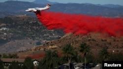 Sebuah pesawat berusaha memadamkan kebakaran di kota Bonsall, California selatan hari Jumat (8/12).