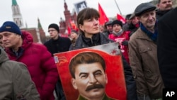 "FILE - Communist party supporters hold portraits of Stalin as they line up to place flowers on his grave in Red Square, outside the Kremlin wall, to mark the 64th anniversary of his death in Moscow, Russia, March 5, 2017. Polls show that Stalin is being increasingly seen by Russian as less a villain and more of an ""effective manager"" and a symbol of Soviet-Russian power."