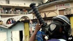 Des policiers couverts de masque lancent des gaz lacrymogènes lors des affrontements avec des manifestants opposés au référendum constitutionnel à Kinshasa, 16 décembre 2005.