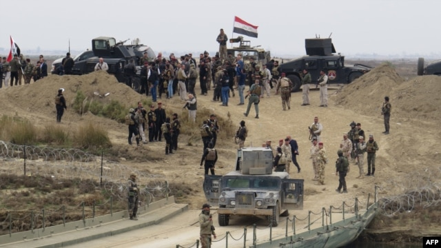 Iraqi security forces gather near a temporary bridge built by the corps of engineers in the Iraqi army south of Ramadi, during a visit by Iraqi Prime Minister Haider al-Abadi on Dec. 29, 2015, after government forces recaptured the city from the Islamic State jihadist group.