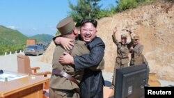 Lãnh tụ Kim Jong Un chúc mừng các khoa học gia quân đội sau vụ phóng thành công phi đạn đạn đạo liên lục địa. (ảnh được thông tấn xã KCNA công bố ngày 5/7/2017.)