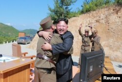 North Korean leader Kim Jong Un reacts with scientists and technicians of the DPRK Academy of Defence Science after the test-launch of the intercontinental ballistic missile Hwasong-14 in this undated photo released by North Korea's Korean Central News Ag