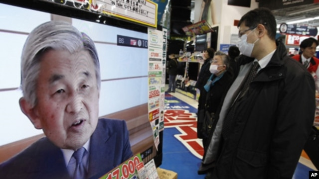 People watch a television broadcasting Japan's Emperor Akihito's televised address to the nation at an electronics retail store in Tokyo, March 16, 2011.