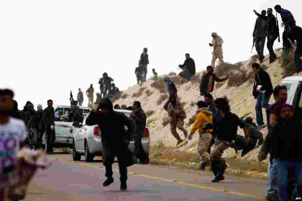 March 31: Rebels run for cover from artillery fired by forces loyal to Gaddafi, near Brega in eastern Libya. (Reuters/Finbarr O'Reilly)