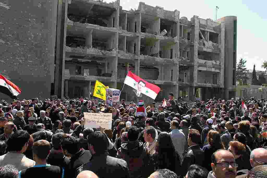 Demonstran melambai-lambaikan bendera Suriah (19/3) saat berkumpul di depan gedung pemerintahan yang hancur akibat pemboman di jalan al-Qassa di Damaskus, untuk mengenang warga yang tewas akibat insiden tersebut sehari sebelumnya (AP).