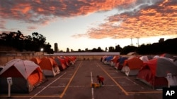 FILE - A boy plays as the sun sets over donated tents for homeless families lined up on a parking lot in the city-sanctioned encampment in San Diego, Nov. 8, 2017. A parking lot in San Diego's famed Balboa Park has acted for the past two months as an unusual triage center. Scores of tents, mobile medical units, portable toilets and showers were brought in to meet the needs of hundreds of people affected by a societal problem that has bloomed into a deadly disaster: homelessness.