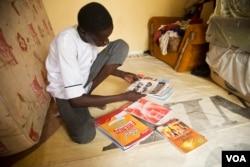 Abdulkadir Abdullahi, 17, looks through his brand-new textbooks in Maiduguri, Nigeria, October 2016. (C. Oduah/VOA)