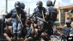 Rioters sit on the back of a police truck after their arrest in Kampala, Uganda, after riots broke out, April 29, 2011