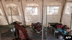 FILE - Patients suffering from cholera receive treatment inside a tent converted into a temporary field hospital near the remote village of Dor, Sudan, April 28, 2017.