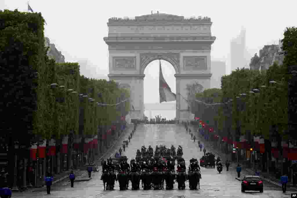 French President Emmanuel Macron's convoy drives up the Champs Elysees to mark Victory Day at the Arc de Triomphe in Paris.