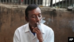 FILE- An Indian man smokes a cigarette in New Delhi, India, Nov. 3, 2016.