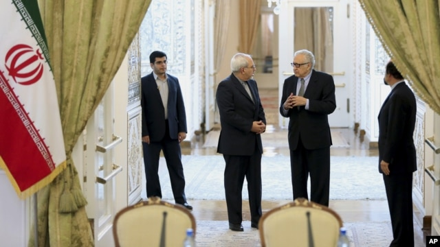 Iranian Foreign Minister Mohammad Javad Zarif, 2nd left, talks with U.N. and Arab League envoy on Syria Lakhdar Brahimi, 2nd right, as they arrive at their joint press conference in Tehran, Iran, Oct. 26, 2013.