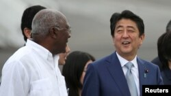 Japan's Prime Minister Shinzo Abe, center, talks to Salvador Antonio Valdes Mesa, a member of the Political Bureau of the Central Committee of the Communist Party of Cuba and vice president of the Council of State of Cuba, upon his arrival at Jose Marti International Airport in Havana, Cuba, Sept. 22, 2016.