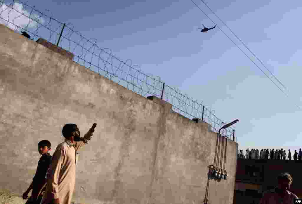 May 4: Residents look at a military helicopter flying over the compound where al Qaeda leader Osama bin Laden was killed in Abbottabad. (Reuters)