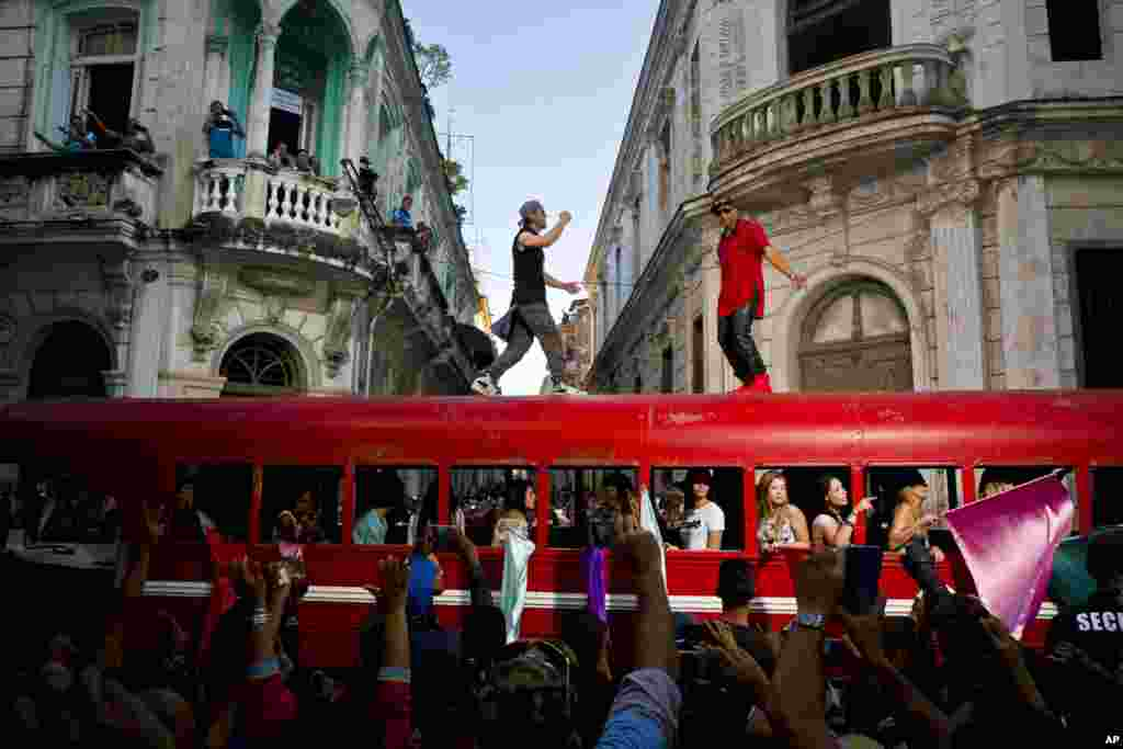 Singer Enrique Iglesias, center, and Cuban singer Descemer Bueno dance on top of a bus during the filming of their video in Old Havana, Cuba
