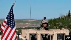 Un soldat américain assis sur son véhicule blindé sur une route menant à la ligne de front tendue à Manbij, Syrie, 4 avril 2018.