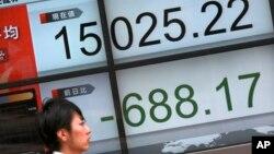 Seorang perempuan melewati papan elektronik menunjukkan posisi indeks saham acuan Japan Nikkei 225 di Tokyo, Jumat (12/2).