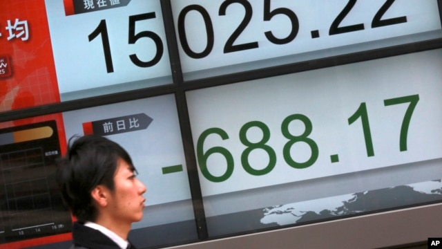 People walk past an electronic stock board showing Japan's Nikkei 225 in Tokyo, Friday, Feb. 12, 2016.