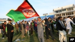 FILE - Afghan cricket fans celebrate the victory of the national cricket team over Zimbabwe as the team returns and celebrates in Kabul, Afghanistan, Oct. 30, 2015.