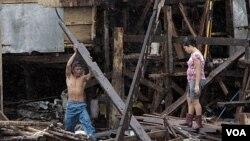 Warga Filipina berusaha mengumpulkan puing-puing rumahnya di Navotas, utara Manila, yang rusak akibat topan Nesat (1/10).