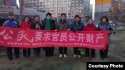 胡佳(右四)等在北京朝阳区闹市区举牌要求中共官员向社会公示财产。(胡佳推特图片)
