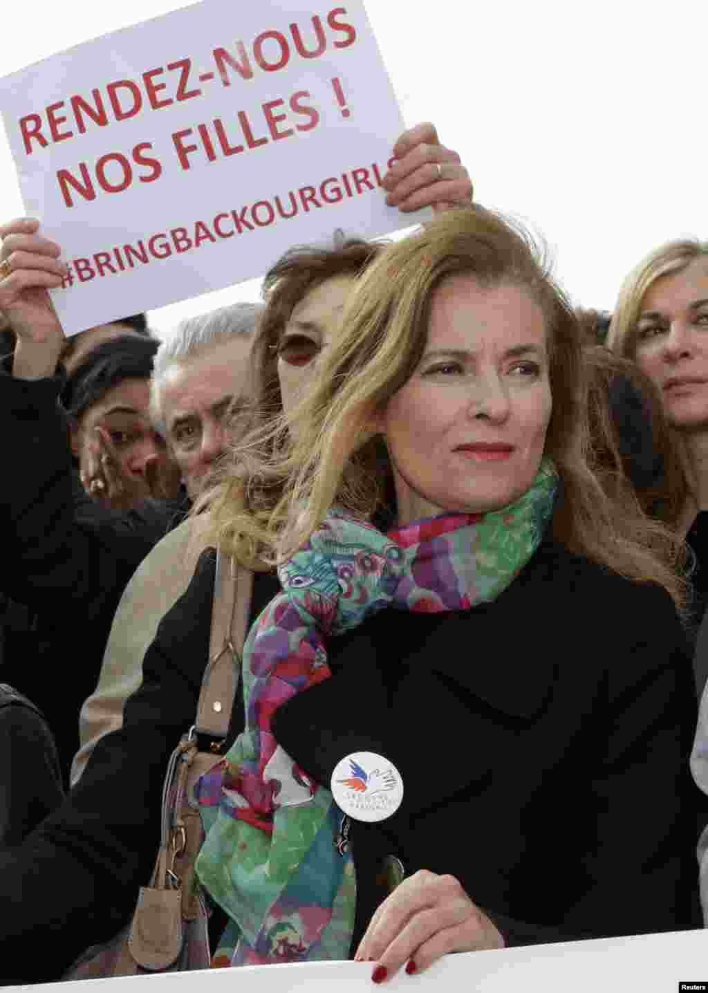 """Former French first lady Valerie Trierweiler stands near a placard that reads """"Bring back our girls"""" during a demonstration to pressure government leaders to help search for the Nigerian schoolgirls, near the Eiffel Tower,Paris, May 13, 2014."""