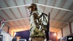 Un militaire libyen est en garde dans une ville à 110 kilomètres de Sirte, Libye le 18 février 2015.