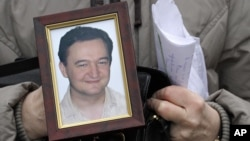 FILE - A portrait of Sergei Magnitsky, who died in jail, is held by his mother Nataliya Magnitskaya, in Moscow, Nov. 30, 2009.