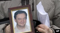 FILE - Photo of a portrait of lawyer Sergei Magnitsky who died in Russian jail.