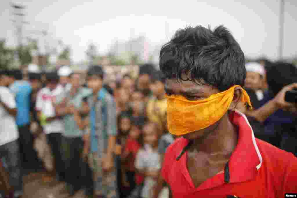 2013年5月1日,人們聚集在一座埋葬著身份不明的服裝廠工人的集體墳場前,一名男孩用布捂著鼻子。這些工人在孟加拉國薩瓦鎮拉納大廈倒塌後喪生。