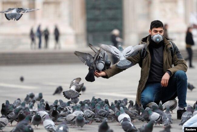 Un hombre con máscara protectora alimenta a las palomas en una plaza de Milán, Italia, el 25 de febrero de 2020.